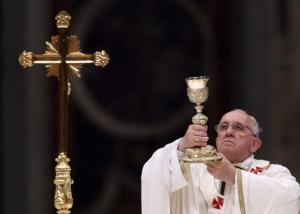 Pope Francis lifts up the chalice as he leads a vigil mass during Easter celebrations at St. Peter's Basilica in the Vatican April 19, 2014. REUTERS/Alessandro Bianchi