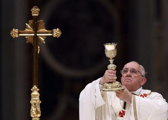 Pope Francis lifts up the chalice as he leads a vigil mass during Easter celebrations at St. Peter's Basilica in the Vatican